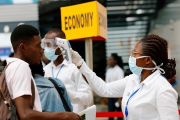 FILE PHOTO: A health worker checks the temperature of a traveller as part of the coronavirus screening procedure at the Kotoka International Airport in Accra, Ghana January 30, 2020. REUTERS/Francis Kokoroko/File Photo - RC2EUE9X5YKK